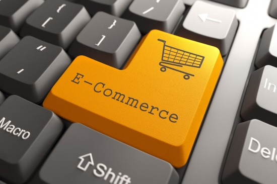 Close up image on a computer keyboard with the Enter key replaced with an orange key that says E-commerce  and features an image of a shopping cart